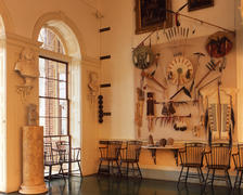 Entrance Hall showing display of recreated Native American objects and Great Clock weights facing east